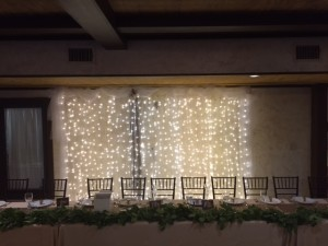 The wedding party table backed by a curtain of lights
