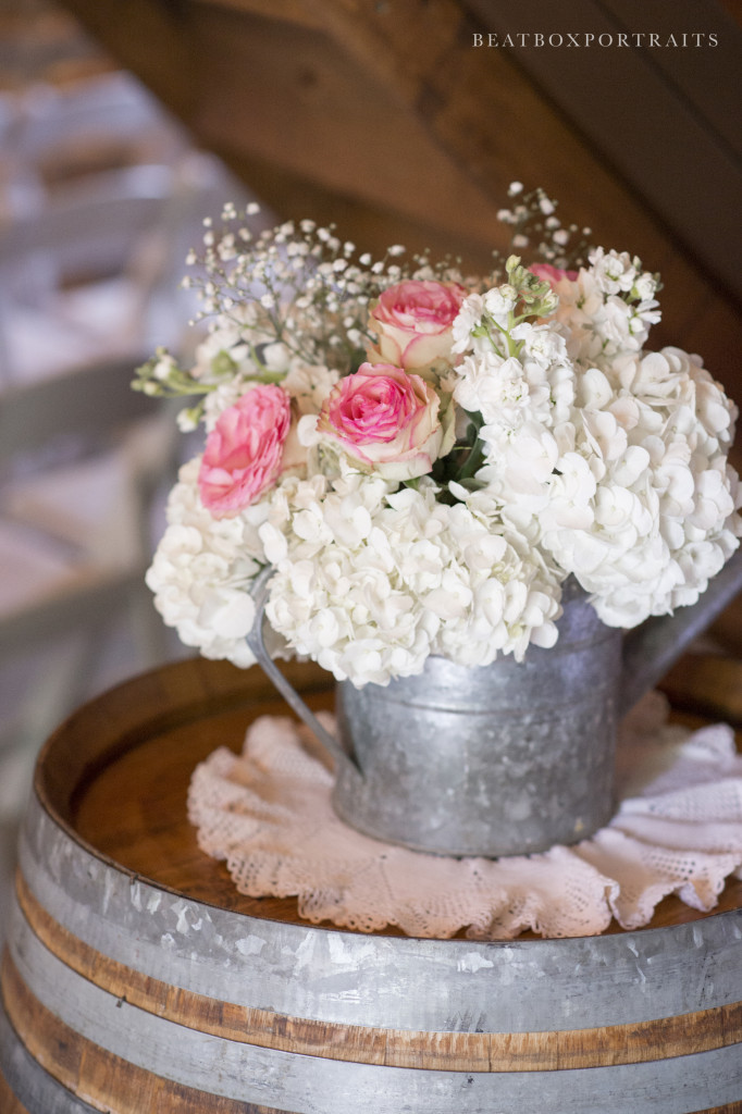 Floral centerpiece in metal pitcher atop a rustic wine barrel