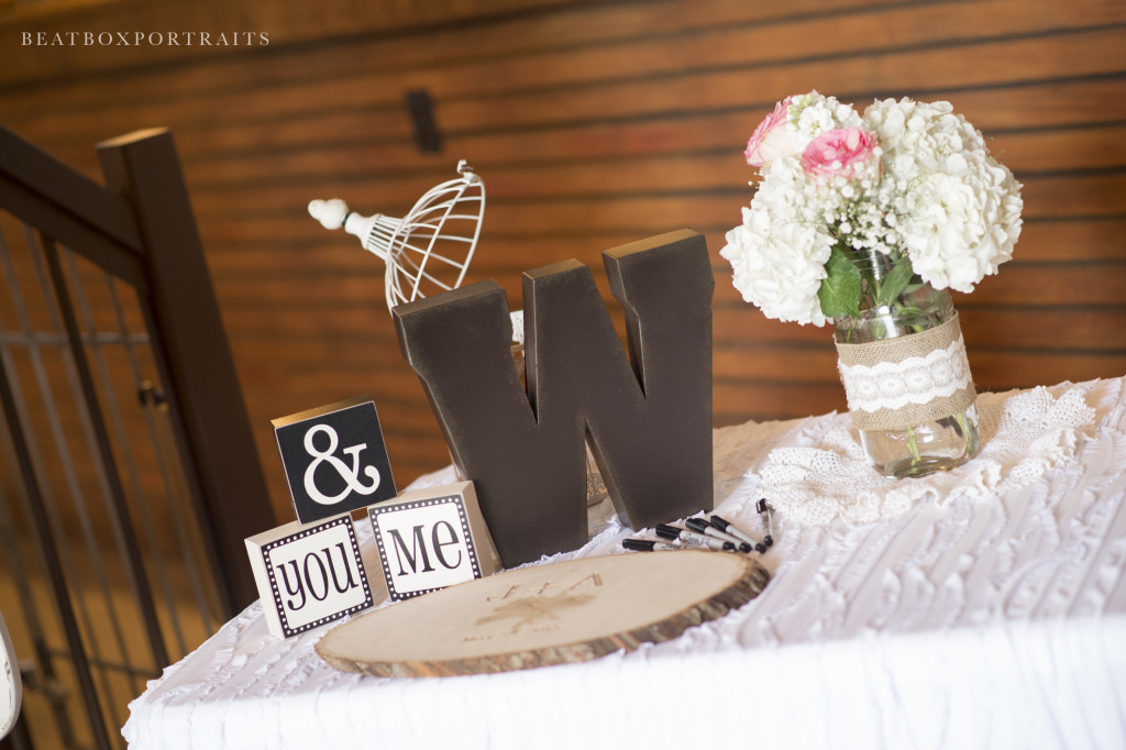 Wedding reception sign-in table with rustic wooden round instead of the traditional book