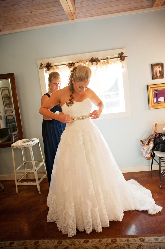 Applying the final details to her wedding dress in Hollow Hill's bridal dressing room