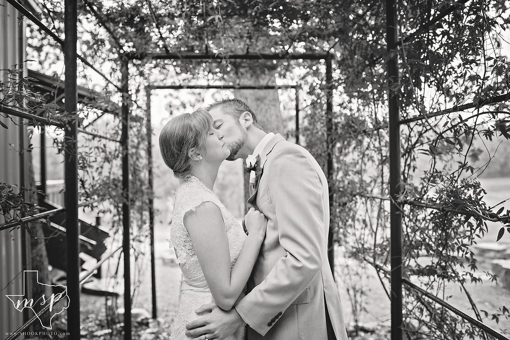 Sharing a kiss under the arbor in the gardens of this outdoor wedding venue
