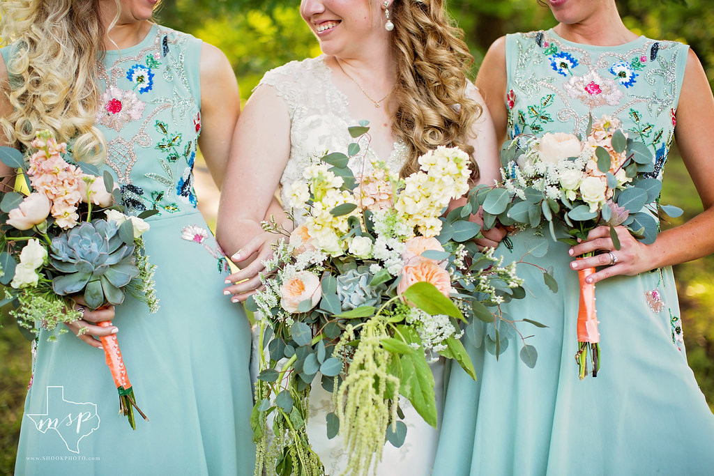 Floral bouquets are echoed in the embroidery of the bridesmaids' dresses