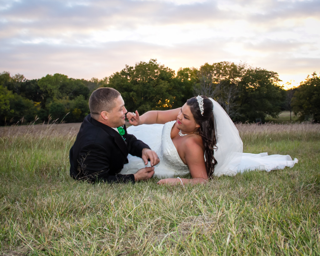 The bride and groom relaxing in the fields in Parker County at this outdoor wedding venue