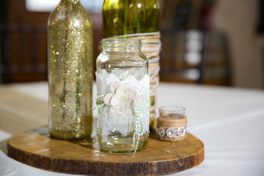 Twine, lace, & glitter adorned glass resting on a wooden round