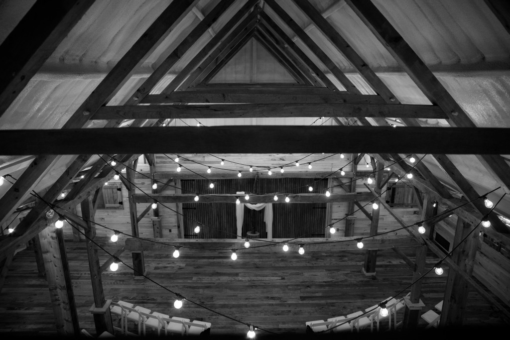 Dimmer controlled stringed lights add ambiance to a rustic barn wedding ceremony