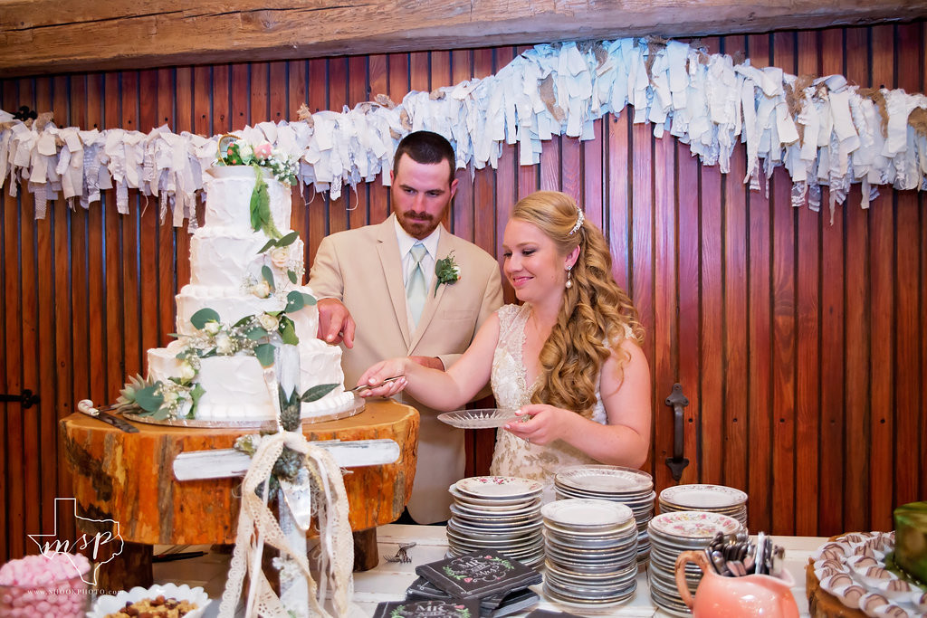 Cutting the cake at their indoor barn reception