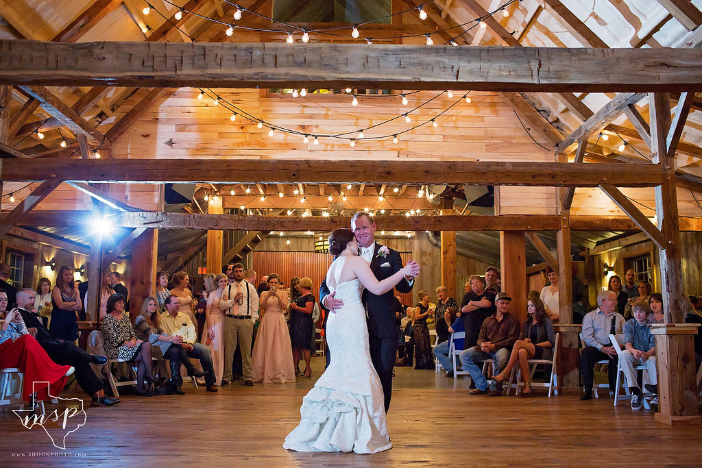 Father and daughter enjoy a dance inside and old-fashioned red barn